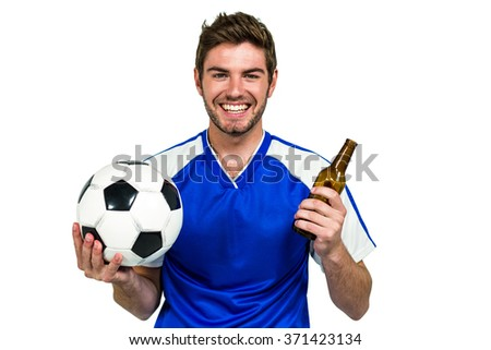 Smiling man holding football and beer bottle on white screen - stock photo