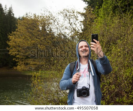Smiling man holding his smartphone