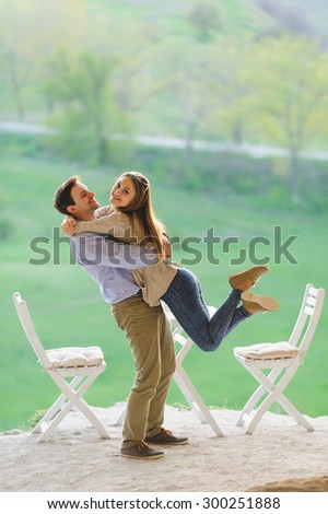 smiling man holding in hands his happy girlfriend - stock photo