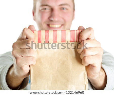 Smiling man holding out a paper bag. Isolated on white - stock photo