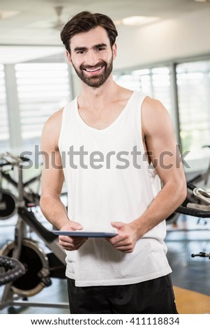 Smiling man holding tablet in the gym - stock photo