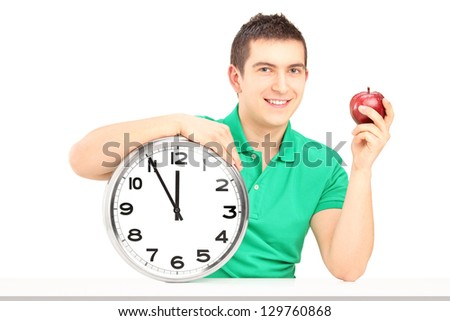 Smiling man holding wall clock and red apple on a table isolated on white background