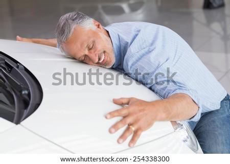 Smiling man hugging a white car at new car showroom - stock photo