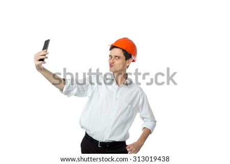 smiling man in a shirt in orange construction helmet make selfie isolate background