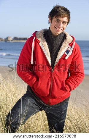 Smiling man in coat on beach - stock photo