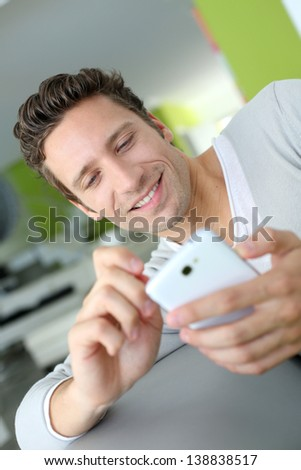 Smiling man in couch using telephone
