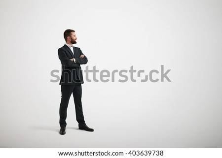 Smiling man in formal wear looking to the side with his arms crossed - stock photo