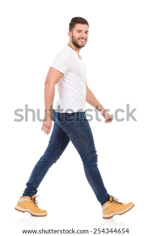 Smiling man in jeans and white t-shirt walking and looking at camera. Full length studio shot isolated on white. - stock photo