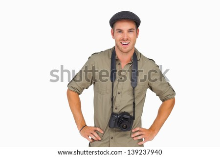 Smiling man in peaked cap with camera around his neck on white background - stock photo