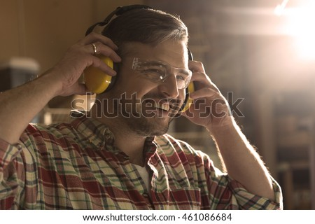 Smiling man in protective goggles assumes headphones