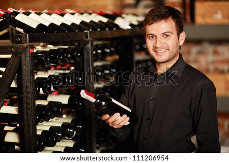 Smiling man in the wine cellar - stock photo