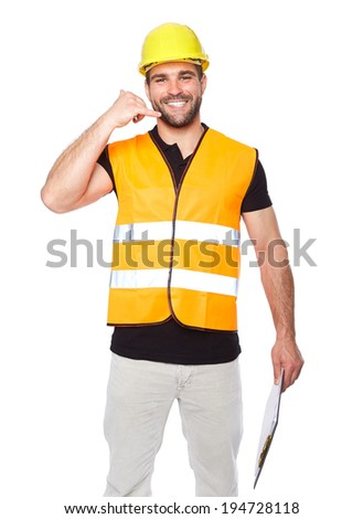 Smiling man in work clothes making a call me sign with his hand - stock photo
