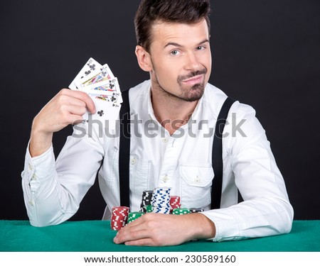 Smiling man is playing poker in casino, looking at the camera. On a black background. - stock photo