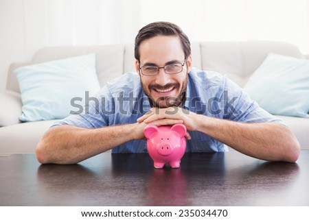 Smiling man laying on the piggy bank in the living room - stock photo