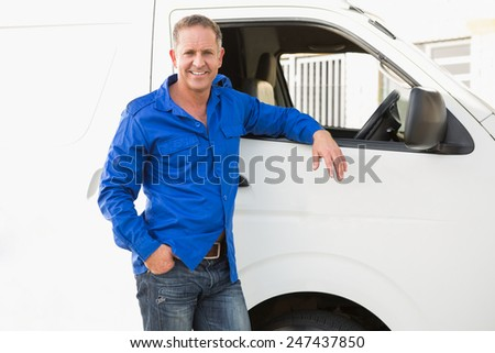 Smiling man leaning against his delivery van outside the warehouse - stock photo