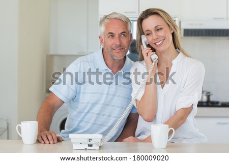 Smiling man listening in on his partners phone call at home in the kitchen - stock photo