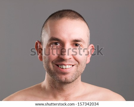 Smiling man looking at camera and isolated on grey background - stock photo