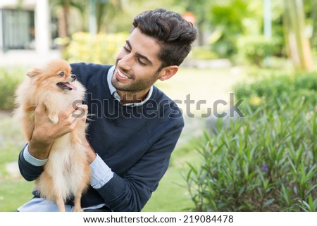 Smiling man looking at Pomeranian spitz in his hands - stock photo