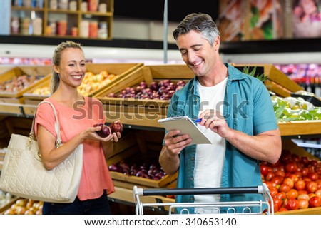 Smiling man looking at the grocery list at the supermarket - stock photo