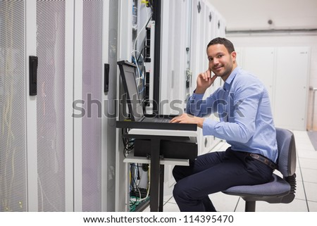 Smiling man looking up from working with servers in data center