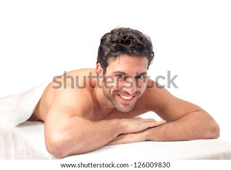 Smiling man lying on a massage table - stock photo