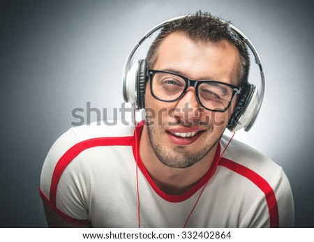 Smiling man make a funny face. Young freak guy with headphones winking to you over dark gray background - stock photo