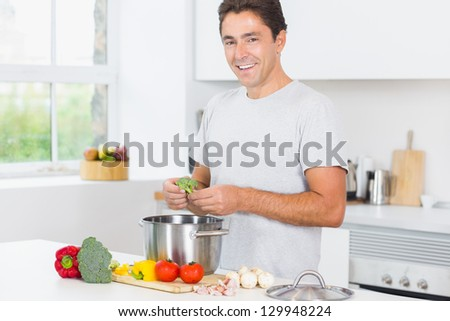 Smiling man making dinner in kitchen