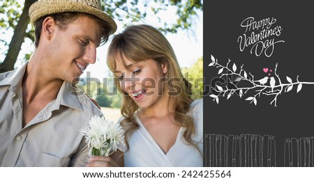 Smiling man offering his girlfriend a white flower in the park against cute valentines message - stock photo