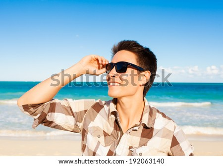 Smiling man on the beach. - stock photo