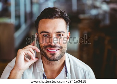 Smiling man on the phone having coffee outside at the coffee shop - stock photo