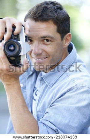 Smiling man photographing with vintage camera - stock photo