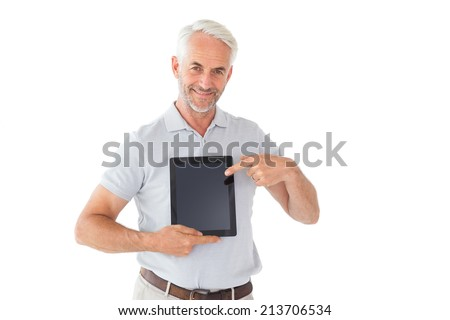 Smiling man pointing to his tablet pc on white background - stock photo
