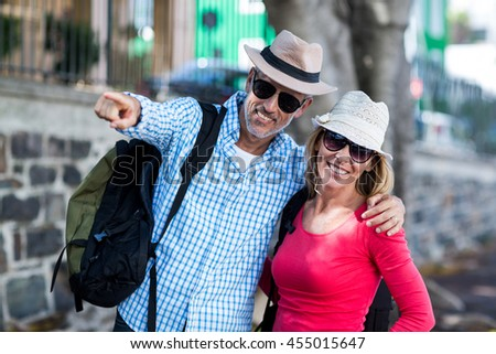 Smiling man pointing while standing with woman on sidewalk in city