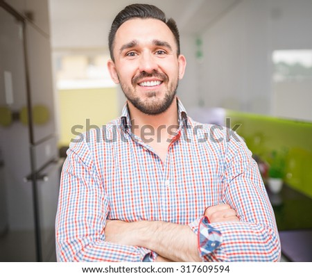 Smiling man preparing fresh smoothie in a food processor - stock photo