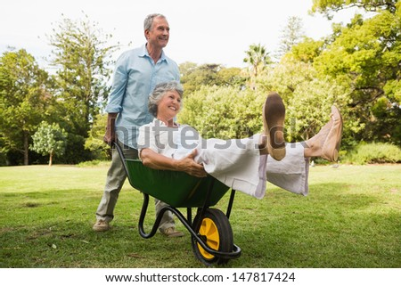 Smiling man pushing his wife in a wheelbarrow having fun outside - stock photo