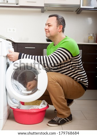 Smiling  man putting clothes in to washing machine  at home
