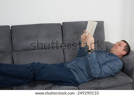 Smiling man reading a book and relaxing on sofa - stock photo