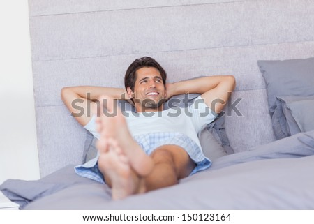 Smiling man resting in his bed