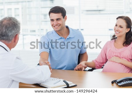 Smiling man shaking hands with his doctor while holding his expecting wifes hand in bright surgery - stock photo
