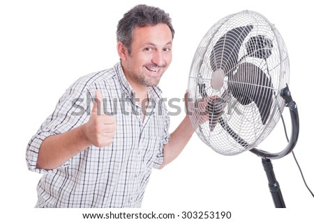 Smiling man showing like gesture in front of blowing cooler as summer heat concept - stock photo
