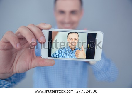 Smiling man showing thumb up and making selfie photo on smartphone - stock photo