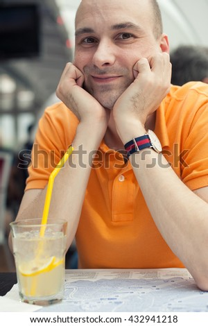 smiling man sits in cafe and drinking cocktail - stock photo