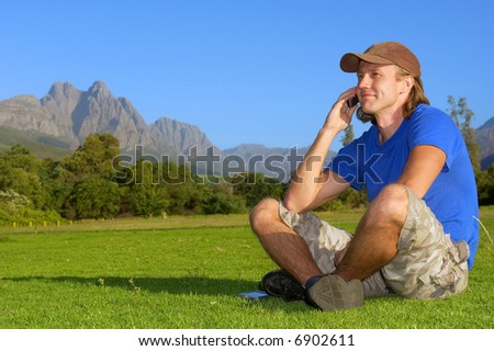 Smiling man sits on grass and talks over phone - and misty mountains are background. Shot in Stellenbosch, South Africa.