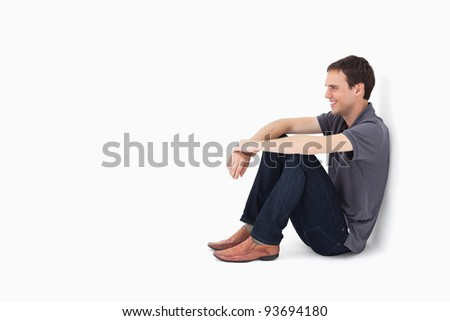 Smiling man sitting against a wall with white background - stock photo