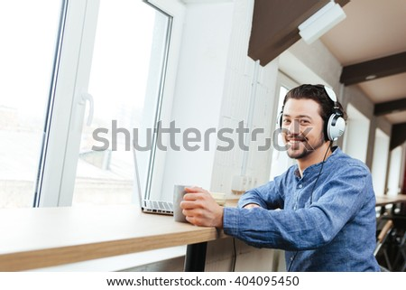 Smiling man sitting at the table with headset and laptop computer and drinking coffee in office - stock photo