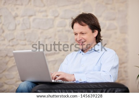 Smiling man sitting in an armchair working on a laptop at home against a painted stone wall with copyspace - stock photo