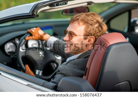 smiling man sitting in white car on the road