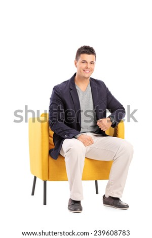 Smiling man sitting on a modern chair isolated on white background