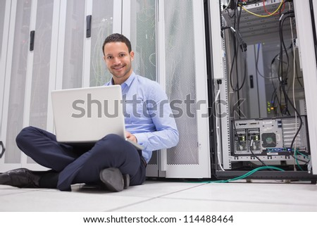 Smiling man sitting on floor checking servers with laptop in data center - stock photo