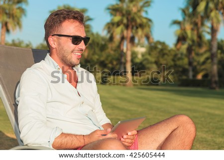 smiling man sitting on long chair holding a tablet and looks away from the camera , in an exotic garden outdoor - stock photo